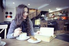Muchacha en el café con el libro Fotos de archivo libres de regalías