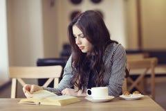 Muchacha en el café con el libro Foto de archivo libre de regalías