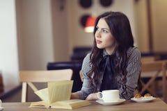 Muchacha en el café con el libro Imagen de archivo