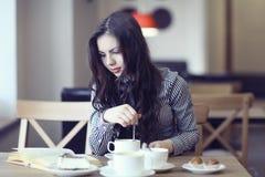 Muchacha en el café con el libro Foto de archivo
