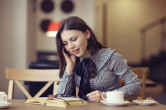 Muchacha en el café con el libro Fotos de archivo