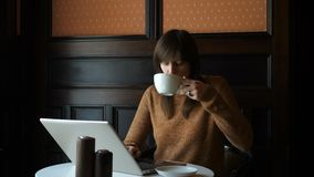 Muchacha en el café con el ordenador portátil almacen de video