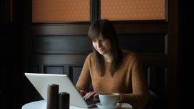 Muchacha en el café con el ordenador portátil almacen de metraje de vídeo