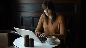 Muchacha en el café con el ordenador portátil metrajes