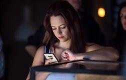 Muchacha en el café que mira el teléfono celular Imagen de archivo