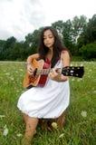 Muchacha en el campo de flor que toca una guitarra Foto de archivo
