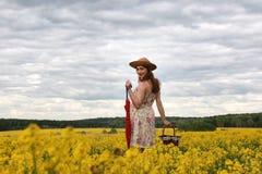 Muchacha en el campo de flores con un paraguas y un sombrero Imágenes de archivo libres de regalías