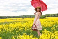 Muchacha en el campo de flores con un paraguas y un sombrero Imagenes de archivo