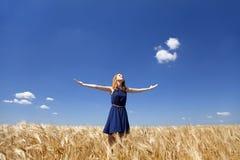 Muchacha en el campo de trigo en día de verano. Imágenes de archivo libres de regalías