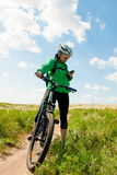 Muchacha en el campo en una bicicleta Fotos de archivo