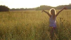 Muchacha en el campo en la puesta del sol almacen de video