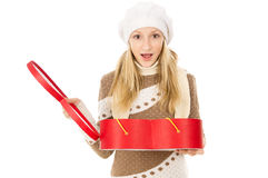 Muchacha en el casquillo del invierno que sostiene un regalo Fotos de archivo