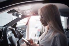 Muchacha en el coche con un móvil Foto de archivo libre de regalías