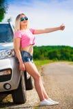 Muchacha en el coche del camino, camiseta rosada, pantalones cortos azules, altura completa, diversión Imágenes de archivo libres de regalías