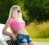 Muchacha en el coche del camino, camiseta rosada, pantalones cortos azules, media altura, atractiva Imagen de archivo libre de regalías