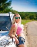 Muchacha en el coche del camino, camiseta rosada, pantalones cortos azules, media altura, atractiva Fotografía de archivo libre de regalías