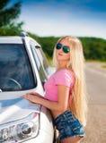 Muchacha en el coche del camino, camiseta rosada, pantalones cortos azules, media altura, atractiva Foto de archivo