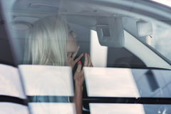 Muchacha en el coche que hace maquillaje Imagen de archivo libre de regalías
