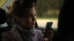 Muchacha en el coche que mira las fotos en su teléfono