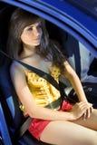 Muchacha en el coche sujetado por el cinturón de seguridad Fotos de archivo
