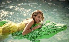 Muchacha en el cocodrilo Mujer atractiva en el mar con el colchón inflable Relájese en piscina de lujo Cocodrilo de la moda foto de archivo libre de regalías