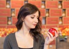 Muchacha en el colmado que sostiene una manzana roja mientras que sonríe imagen de archivo