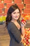 Muchacha en el colmado que sostiene una manzana roja mientras que sonríe imagenes de archivo