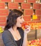 Muchacha en el colmado que sostiene una manzana roja mientras que sonríe imagen de archivo libre de regalías