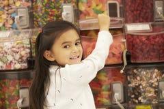 Muchacha en el contador del caramelo en supermercado Imagen de archivo