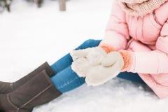 Muchacha en el día nevoso del invierno, manoplas hechas punto calientes y botas de una mujer sentándose en la nieve y haciendo la foto de archivo libre de regalías