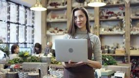 Muchacha en el delantal que sostiene un ordenador portátil en sus manos, tipos algo y sonrisas almacen de metraje de vídeo