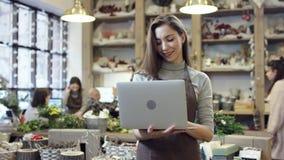 Muchacha en el delantal que sostiene un ordenador portátil en sus manos, tipos algo y sonrisas, ella mira a veces para arriba almacen de video