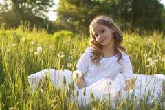 Muchacha en el dundelion blanco del soplo del vestido Imagenes de archivo