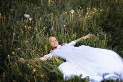 Muchacha en el dundelion blanco del soplo del vestido Imagen de archivo libre de regalías