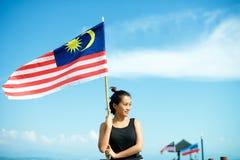 Muchacha en el embarcadero con la bandera malasia Imagenes de archivo