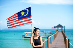 Muchacha en el embarcadero con la bandera malasia Fotos de archivo libres de regalías