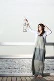 Muchacha en el embarcadero con la lámpara de keroseno Imagen de archivo libre de regalías
