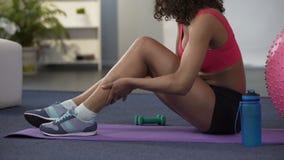 Muchacha en el equipo del gimnasio que se sienta en piso y que da masajes a la pierna encogida, músculo filtrado metrajes