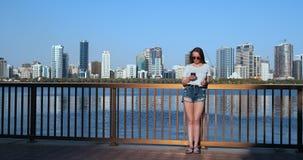 Muchacha en el fondo de la ciudad grande y de la bah?a que sostienen un smartphone en gafas de sol metrajes