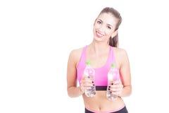 Muchacha en el gimnasio que sostiene las botellas de agua Foto de archivo libre de regalías