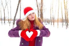 Muchacha en el invierno que lleva a cabo un corazón nevoso Imagen de archivo