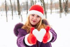 Muchacha en el invierno que lleva a cabo un corazón nevoso Foto de archivo