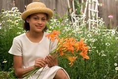Muchacha en el jardín con el sombrero de paja Fotografía de archivo libre de regalías