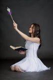 Muchacha en el juego de la hada con la varita mágica en negro Fotos de archivo