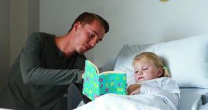 Muchacha en el libro de lectura de la cama con su padre metrajes