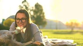 Muchacha en el libro de lectura de los vidrios que se acuesta en una manta en el parque y los pequeños funcionamientos del perro  almacen de metraje de vídeo