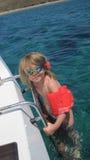 Muchacha en el mar con los brazales Foto de archivo