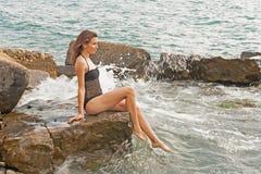 Muchacha en el mar que se sienta en las rocas Fotos de archivo