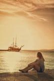 Muchacha en el muelle en el mar que mira la nave Fotografía de archivo
