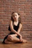 Muchacha en el negro que se sienta cerca de la pared de ladrillo Imagen de archivo libre de regalías